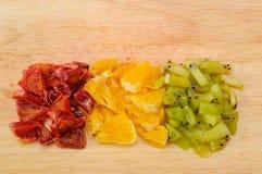 Snittskivor av den röda och orange apelsin- och kiwicloseupen på skärbräda Arkivbild