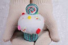糖果土地圣诞节 在白色的女性手编织了拿着在一白色sno的舒适手套五颜六色的杯形蛋糕圣诞树装饰 库存图片