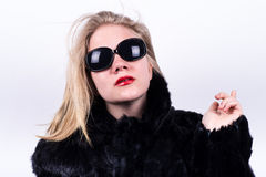 Upper class girl in dark sunglasses, red lipstick and fur. Snobbish upper class girl in dark sunglasses, red lipstick and fur pointing behind hem on a white royalty free stock photography