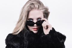 Snobbish upper class girl in dark sunglasses and fur. Snobbish upper class girl looking out from behind her dark glasses. Wearing a black fur jacket with a white stock images