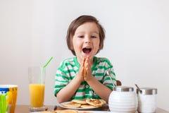 Snoepje weinig Kaukasische jongen, die pannekoeken eten Stock Afbeelding