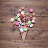 Snoepjes in een wafelkegel op houten achtergrond Stock Afbeeldingen