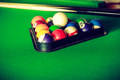 Snooker ball and stick on billiard table. Billiard balls and cue stick on green table. Pool game Royalty Free Stock Photo