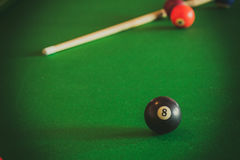 Snooker ball and stick on billiard table. Billiard balls and cue stick on green table. Pool game Stock Photo