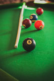 Snooker ball and stick on billiard table. Billiard balls and cue stick on green table. Pool game Stock Photography