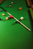 Snooker ball and stick on billiard table. Billiard balls and cue stick on green table. Pool game Royalty Free Stock Photos