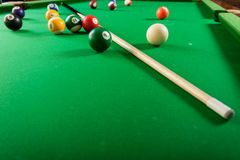 Snooker ball and stick on billiard table. Billiard balls and cue stick on green table. Pool game Royalty Free Stock Image