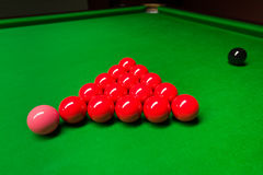 Snooker balls on green table. Red snooker balls prepared for the game on green table. Pink ball in front of the red balls and black ball way behind. Snooker game stock images