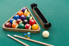 Snooker billards pool balls, cue, brush, chalk on green table. Snooker billards pool balls in triangle, chalk, cue, extender stick and brush on green table Royalty Free Stock Images