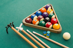 Snooker billards pool balls, cue, chalk on green table. Snooker billards pool balls in triangle, chalk, cue, extender stick on green table Stock Photo