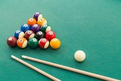 Snooker billards pool balls, cue, extender stick on green table. Snooker billards pool balls in triangle and cue and extender stick on green table Stock Photo