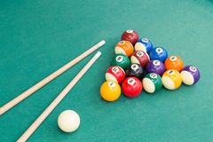 Snooker billards pool balls and cue stick on green table. Snooker billards pool balls in triangle and cue stick on green table Royalty Free Stock Image