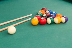 Snooker billards pool balls and cue stick on green table. Snooker billards pool balls in triangle and cue stick on green table Stock Photography