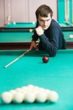 Snooker billiard player. Young player man with cue at the begining of billiard snooker game Royalty Free Stock Image