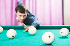 Snooker billiard player. Young player man with cue playing billiard or snooker game Royalty Free Stock Photo