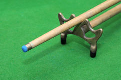 Snooker cue with rest  on green background Stock Images