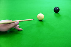 Snooker. A photo of a cue on a hand that is shooting a black ball in a snooker game Royalty Free Stock Images