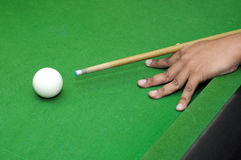Snooker player with billiard cue ready to hit white ball with selective focus Stock Photos