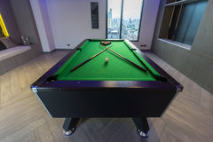 Snooker Pool Billiards green table with complete set of balls and two pool cues in a modern games room. Snooker, billiards, or pool table, green and black color Royalty Free Stock Photo