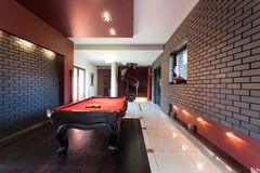 Snooker table in luxury interior. Snooker table in a luxury interior with brick walls stock photo
