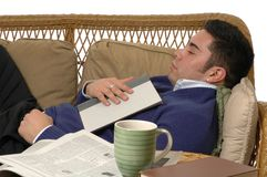 Snooze. A man napping on the sofa with a book on his lap Stock Images