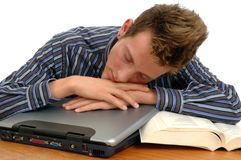 Snooze. A young man sleeping on top of his laptop computer Royalty Free Stock Photo