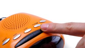 Snooze Alarm. Finger pressing a snooze alarm button Royalty Free Stock Photography