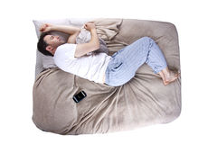 Snoozing Alarm. Man snoozing modern cell phone alarm clock Royalty Free Stock Photo