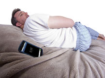 Snoozing Alarm. Man snoozing modern cell phone alarm clock Royalty Free Stock Image