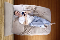 Snoozing Alarm. Man snoozing modern cell phone alarm clock Stock Photography