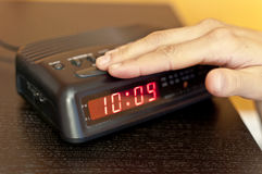 Snoozing the morning alarm. Hand pressing the snooze button on a digital alarm clock Royalty Free Stock Photos