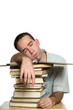 Snoozing Student. A student who fell asleep on his pile of books, isolated against a white background Royalty Free Stock Photography