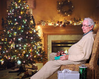 Snoozing by the Tree. A senior man snoozing in his living room decorated for the holidays Stock Image
