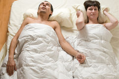 Snoring. Couple in bed with man snoring Royalty Free Stock Image