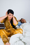Snoring. Couple in bed with woman awake and nervous because can't sleep and holding hands on ears while man sleeping and snoring,check Couples Royalty Free Stock Image