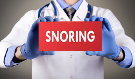 Snoring. Doctor`s hands in blue gloves shows the word snoring. Medical concept Stock Photo