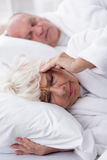 Snoring husband and his wife. Image of snoring husband and his wife with headache Royalty Free Stock Photo