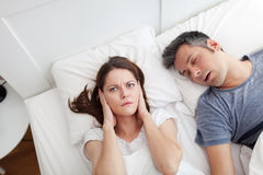 Snoring husband. Woman covering ears, annoyed by the snoring of her husband royalty free stock photo