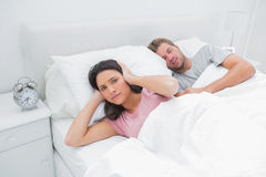 Snoring man is annoying his wife who tries to sleep. Snoring men is annoying his wife who tries to sleep in her bed stock photo