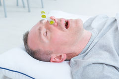 Snoring man in bed. With cloth clip on his nose Stock Image