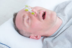 Snoring man in bed. With cloth clip on his nose Royalty Free Stock Photos