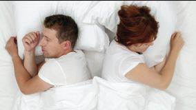 Snoring man choking out loud waking his wife up during the noisy night and she close ears with pillow. view from above. Snoring man choking out loud waking his stock footage