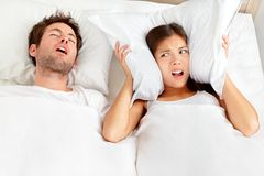 Snoring man - couple in bed. Snoring man. Couple in bed, men snoring and women can not sleep, covering ears with pillow for snore noise. Young interracial couple stock images