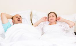 Snoring man, frustrated woman. Snoring man. Couple in bed, men snoring and women can not sleep, covering ears with hands for snore noise. Middle aged couple Stock Image