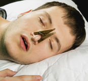 Snoring. A snoring of man with pin on nose Royalty Free Stock Photo