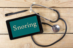 Snoring - Workplace of a doctor. Tablet, medical stethoscope, black pen on wooden desk background. Top view Stock Photos