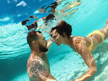 Snorkel couple looking at each other underwater in blue ocean Royalty Free Stock Images