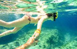 Snorkel couple swimming together in tropical sea underwater royalty free stock photography