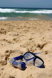 Snorkel gear on beach. A view of swim goggles and a snorkel tube lying in the sand near the water on a sunny beach Stock Photography