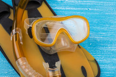 Snorkel gear. Orange snorkel gear - snorkel, mask and flippers - on a blue background Royalty Free Stock Photos